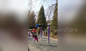 Old Chinese man swinging on horizontal bar knocks down girl walking by
