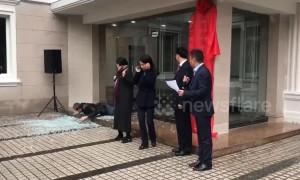 Cartoon-ish scene as man walks into glass door, shattering it during ceremony