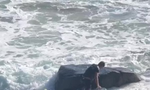Surfer Struggles Against Pounding Waves