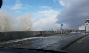 Waves crash over seafront onto passing cars in New Brighton in UK