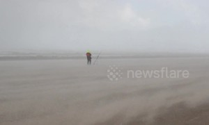 Dramatic moment storm hits Northern Ireland coast, leaving beach-goers battling horizontal hail and sand