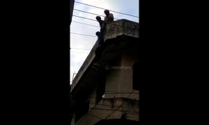 Dumb thief stuck dangling from top of building is rescued by police
