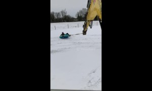 Workers take a spin in the snow with aid of excavator