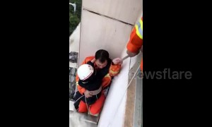 Firemen save girl hanging out of window on third floor of residential building