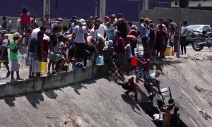 Scores of Venezuelans collect water from river as power outage crisis continues