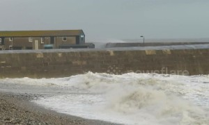 Waves break over harbour wall in Lyme Regis during Storm Freya