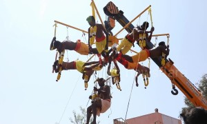 Hindu devotees display their devotion by piercing skin with metal hooks and hanging from crane