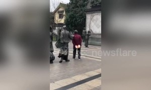Chinese granny uses pointy finger on statue to scratch her back