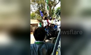 Men drink beer on tractor while canvasing for prohibition candidate in India