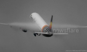 Condensation clouds engulf plane's wings as it takes off from Manchester Airport