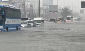 Cars travel through flooded roads in Thai city