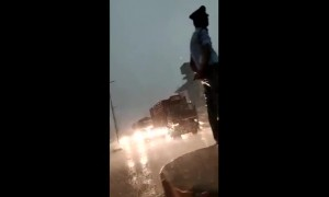 Neither wind nor rain stops this Indian traffic cop from doing his job