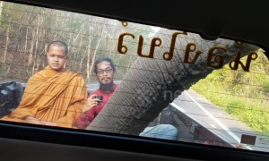 Terrified Buddhist monk looks on nervously as wild ELEPHANT raids pickup truck