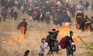 Refugees in Greece start fires as they clash with police in attempt to reach northern border