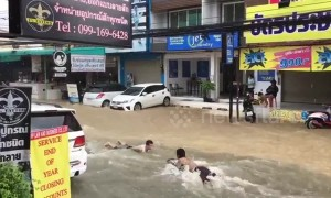 Boys go bodyboarding on flooded road in Thailand