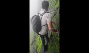 Trekker shows off terrifyingly slippery climb along cliff edge in west India