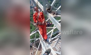 Chinese electrical workers nap on 50-metre-high transmission tower