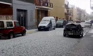 Unseasonal hailstorm pummels cars parked on a street in Barcelona