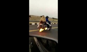 Indian family rides down highway on burning motorbike