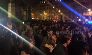 Parisians gather and sing hymns on the Tournelle Bridge opposite Notre Dame