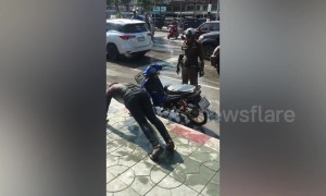 Policeman makes motor scooter rider do push-ups as punishment