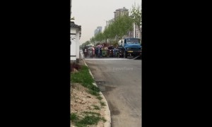 Bizarre moment moped riders patiently drive behind van spraying water in China