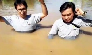 Indonesian residents struggle to walk through submerged road amid devastating flooding