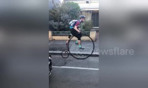 Melbourne man in full cycle gear surprises commuters on Penny-farthing