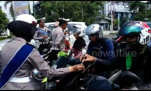 Indonesian police remind road users to take care by handing out flowers