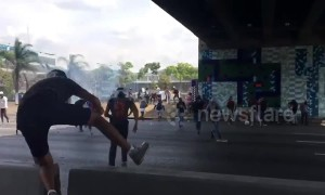 Clashes in Caracas continue as rocks are thrown at motorcyclists and huge fences are destroyed