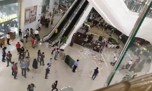 Debris plunges from fifth floor escalator as heavy rain batters Philippines shopping mall