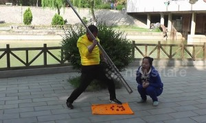 Chinese man uses giant chopsticks to feed fruit to woman
