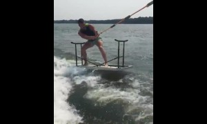 Guy water skies on top of folding table