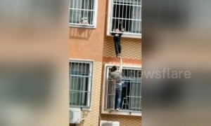 Heroic Chinese man holds up boy hanging from seventh-floor window until help arrives