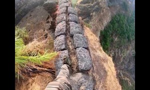 Trekker takes a high risk walk along edge of a mountain fort in central India