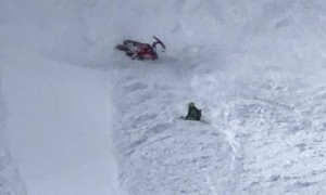 Snowmobile Rider Takes a Spill Down the Hill