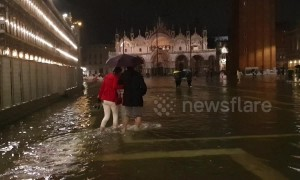 Tourists forced to wade as unusually high tide floods Venice