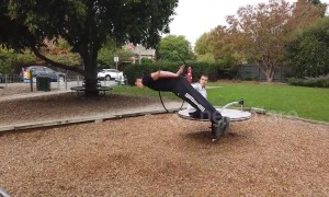 Threading the needle! Acrobat leaps through hoop spinning on playground turntable