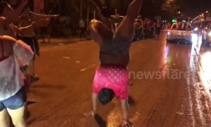 Exuberant man celebrates Thai New Year by performing dance routine in the middle of road