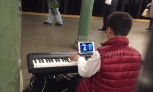 Child prodigy plays Mozart masterpiece while playing a computer game at the same time in New York, USA