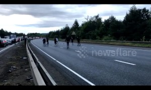Football fans play kick-about during traffic gridlock on closed M1