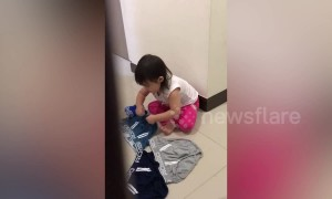 Adorable little girl secretly helps with the laundry