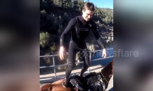 US man performs double front flip from horse's back off a bridge