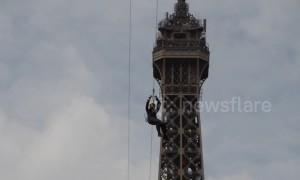 Brave thrill-seekers ride a 377-foot zipline off the Eiffel Tower
