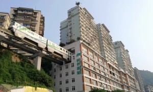 Elevated trainline runs through hole in building in China's Chongqing