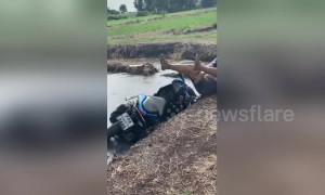Wheelie bad! Thai man fails at moped trick and falls in pond