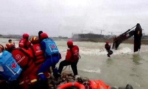 Chinese firefighters rescue workers trapped on flooded digger