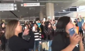 K-pop group NCT 127 surrounded by fans as they arrive at LAX, Los Angeles