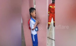 Chinese firemen expand the gap between 2 pillars to free trapped boy