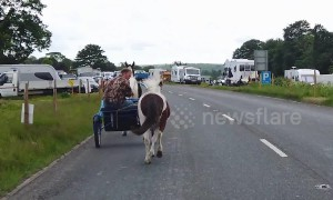 Travellers ride their horse-drawn carts ahead of the Appleby Horse Fair